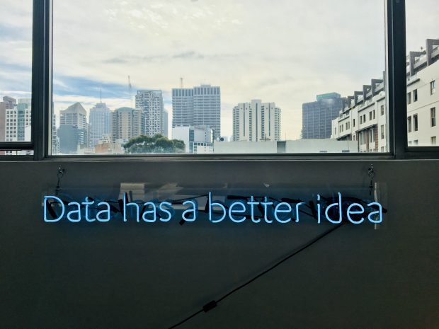 """A neon sign reading """"data has a better idea"""" with a cityscape in the background"""