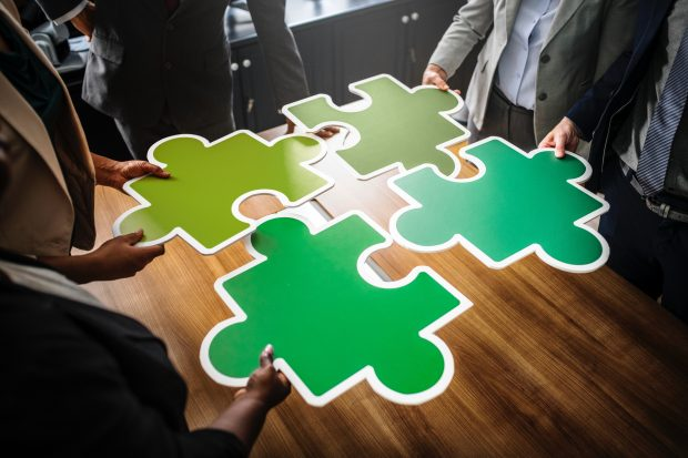 business people standing around a table holding giant plastic jigsaw pieces